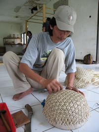 Indonesian weaver preparing the dome shape of the basket with a mold.